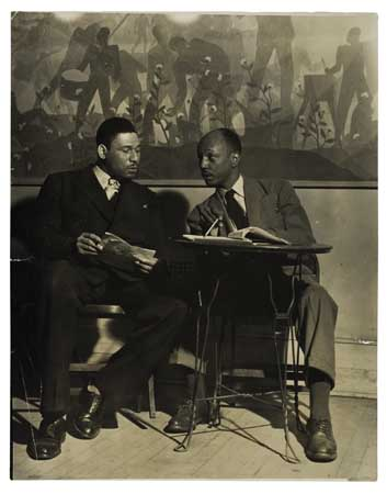 (THEATRE.) Frederick O'Neal and Abram Hill (?) seated in front of Aaron Douglas's mural at the Schomburg Center
