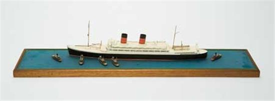"""(CUNARD LINE.) """"Mauretania"""" (II). Wonderful hand-crafted wooden model of the ship escorted by tugs, by VAN RYPER."""