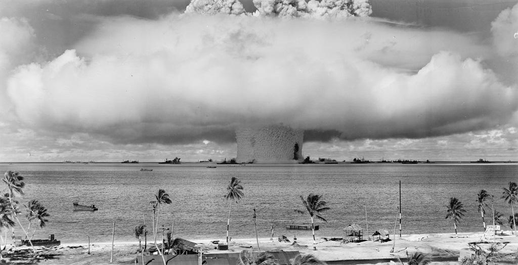 (NUCLEAR TESTING--BIKINI ATOLL) Mini-archive with 13 rare photographs illustrating the immense power of the Bikini Atoll atomic bomb te