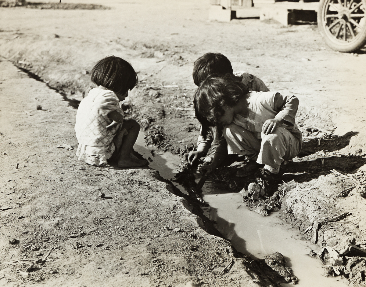 DOROTHEA LANGE (1895-1965) Mexican children playing in ditch which runs through company cotton camp near Corcoran, Calif.