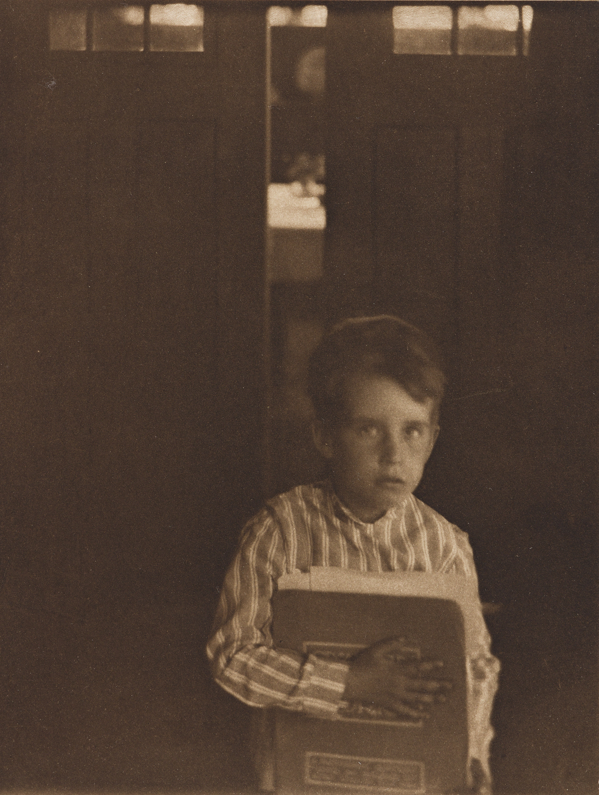 CLARENCE WHITE (1871-1925) Boy with Camera Work, from Camera Work Number 9.
