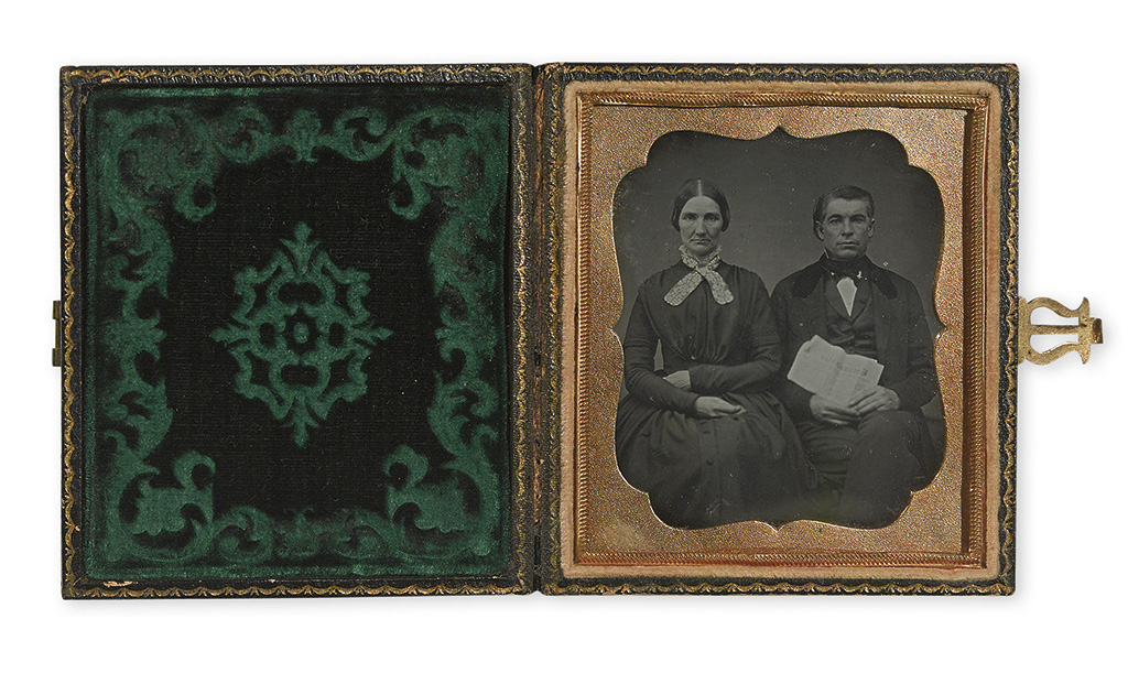 (PHOTOGRAPHY--CASED IMAGES.) Man and wife holding a copy of the Emancipator.