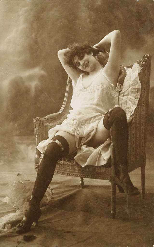 (POSTCARDS) An album containing 54 risqué real photo postcards and photographs featuring female subjects,