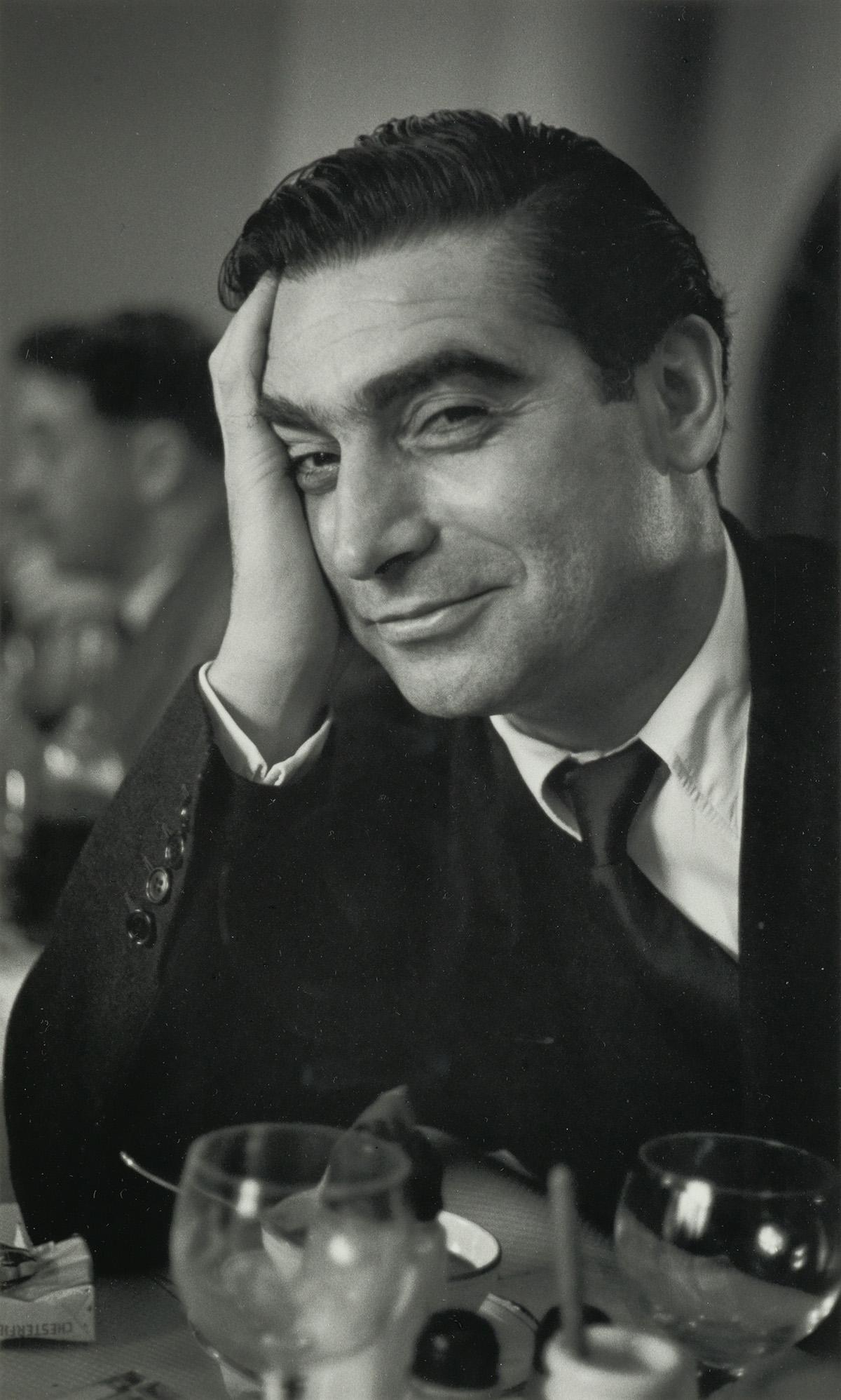 RUTH ORKIN (1921-1985) Robert Capa at Magnum luncheon, Paris.
