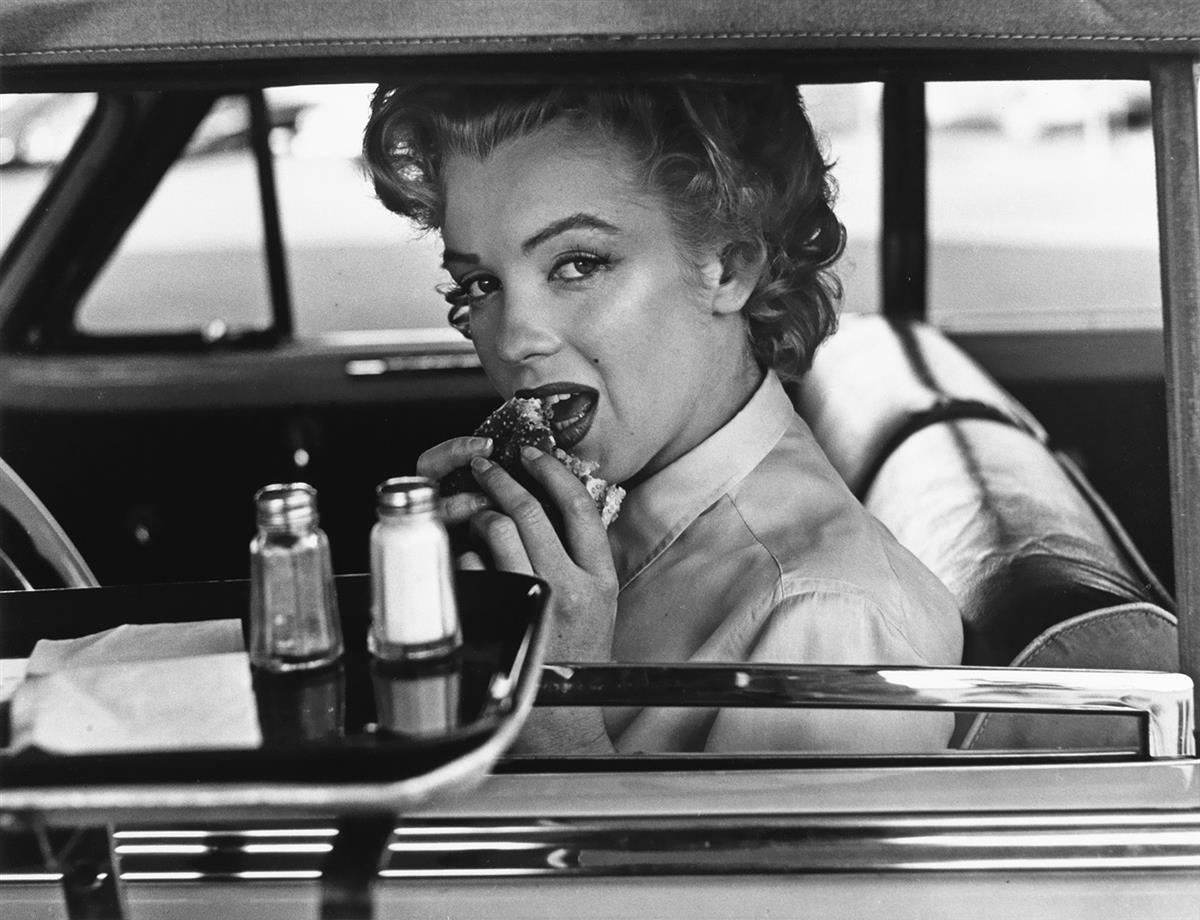 (PHILIPPE HALSMAN) (1906-1979)/STEPHEN GERSH (active 1980s) Marilyn Monroe eating a hamburger at a drive-in.