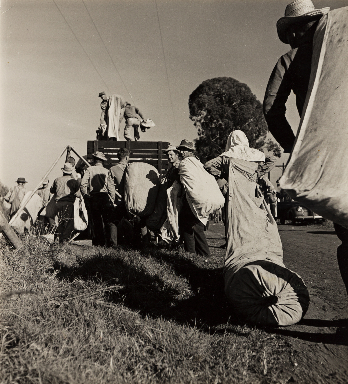 HANSEL MIETH (1909-1998)/OTTO HAGEL (1909-1973) Cotton pickers lining up for weighing in Visalia, California.
