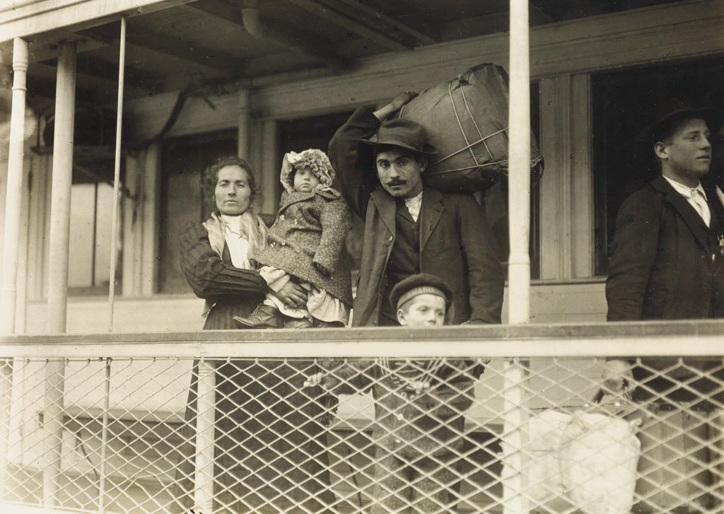 LEWIS W. HINE (1874-1940) Italian family on the ferry boat landing at Ellis Island.