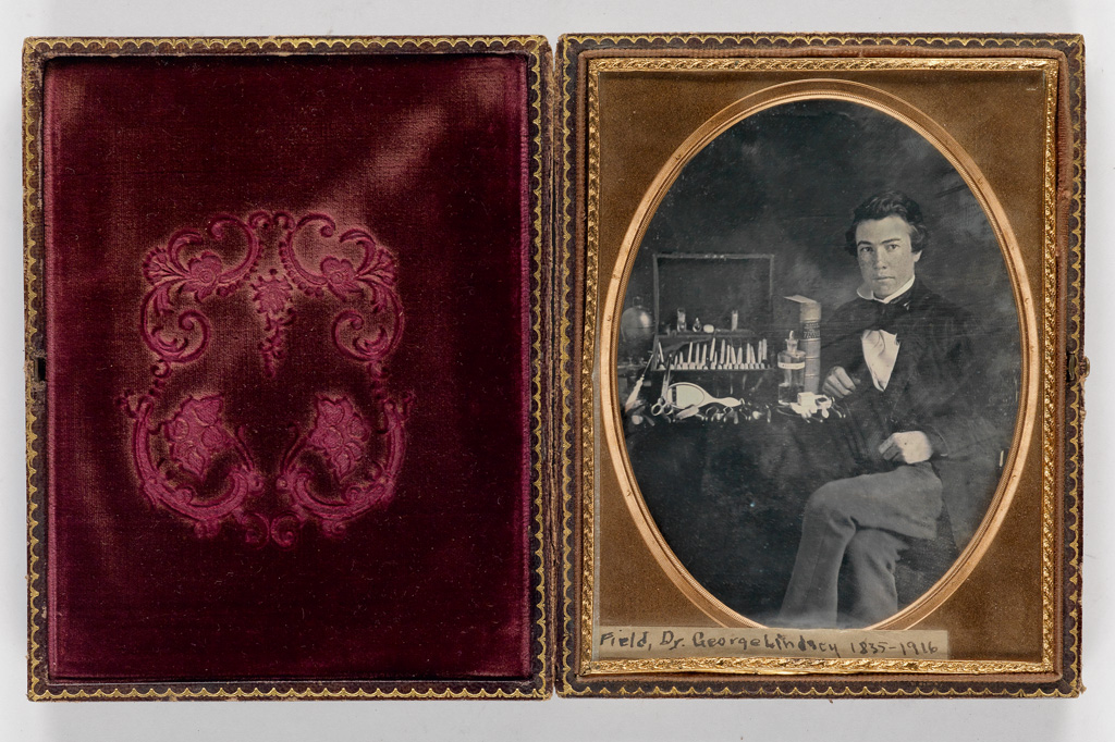 (DENTISTRY) Half-plate daguerreotype of Dr. George Lindsey Field (1835-1916), who is proudly posing with a range of dental tools.