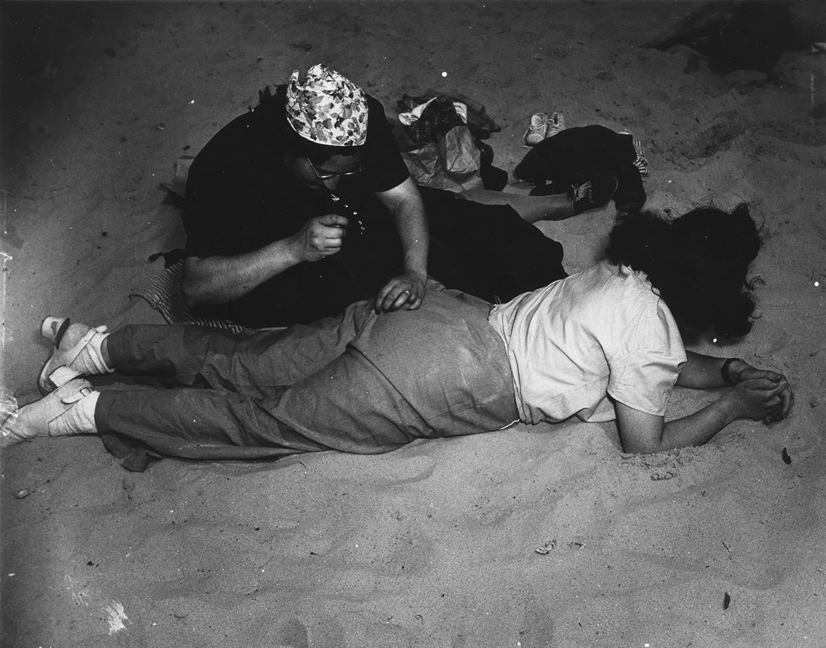 WEEGEE-[ARTHUR-FELLIG]-(1899-1968)-Sewing-Pants-Coney-Island