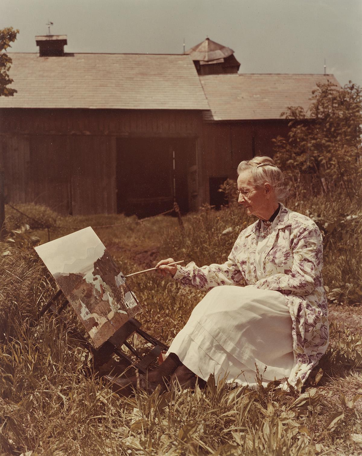 HARRY WARNECKE (1900-1984) Grandma Moses painting a scene.