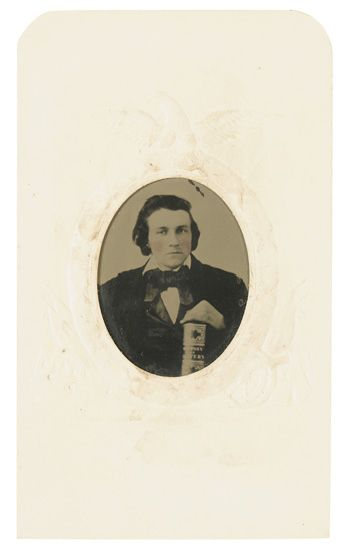 """(SLAVERY AND ABOLITION.) [BLAKE, W. O.] Tintype photograph of a young man holding a copy of W. O. Blake''s """"""""History of Slavery and t"""