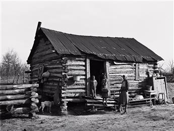 RUSSELL LEE (1903-1986) Mother with three children in front of log house.