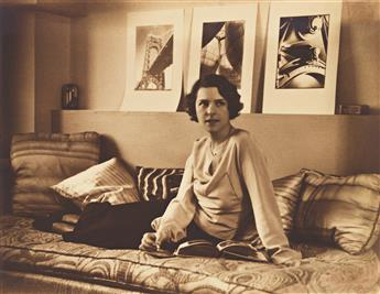 H. RICHARDSON CREMER (active 1920s-40s) Portrait of Margaret Bourke-White with her photographs behind her.