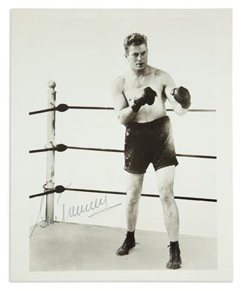 GENE TUNNEY. Photograph Signed, full-length portrait showing him in the ring with gloves raised. Signed in the i...