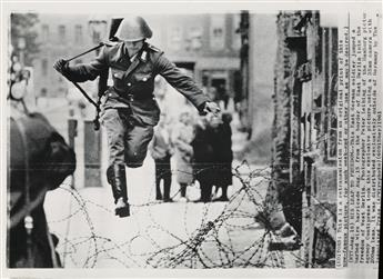 PETER LEIBING (1941-2008) Leap into Freedom [East German soldier Hans Conrad Schumann jumping barbed wire barricade to freedom as he de