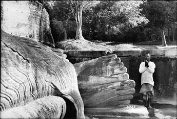 HENRI CARTIER-BRESSON (1908-2004) Praying at the foot of Buddha, Sri Lanka.