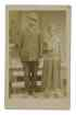 Real photo-postcard of a man and woman standing in front of the porch of a house,