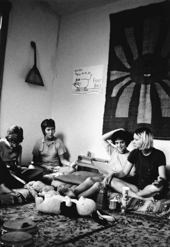 JOAN E. BIREN (1944 - )  Charlotte Bunch with members of the Furies in the living room of one of their collective houses.