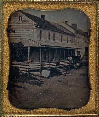 (OUTDOOR SCENE) Sixth-plate daguerreotype depicting a street scene in which several men are posing on the porch of a clapboard building